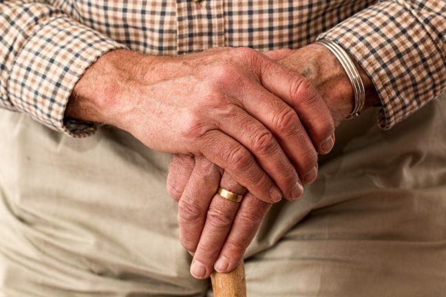 elderly man's hands resting on a walking stick