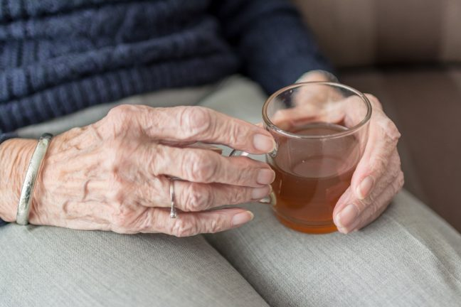 elderly hands holding a teacup