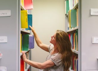 A Caxton staff member looks through shelves of files