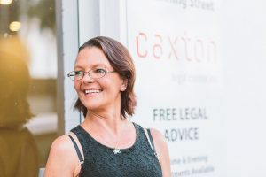 "A caxton client stands in front of the ""Free Legal Advice"" sign at Caxton Legal Centre"