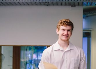 A law student at Caxton reception smiles at the camera
