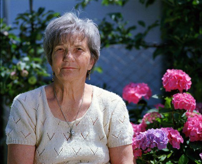 senior woman sitting amongst flowers
