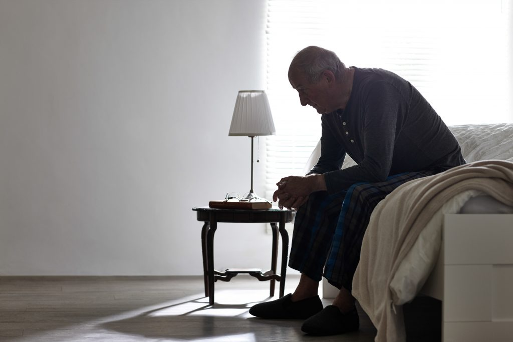 Older man sitting on bed